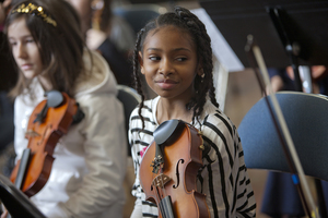 An ensemble student smiles while listening to her peers practice