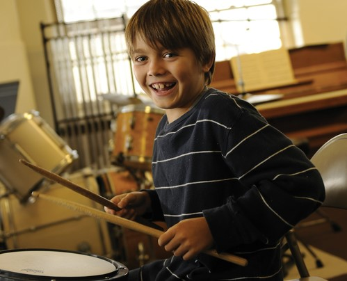 A Settlement student smiles while practicing the drums