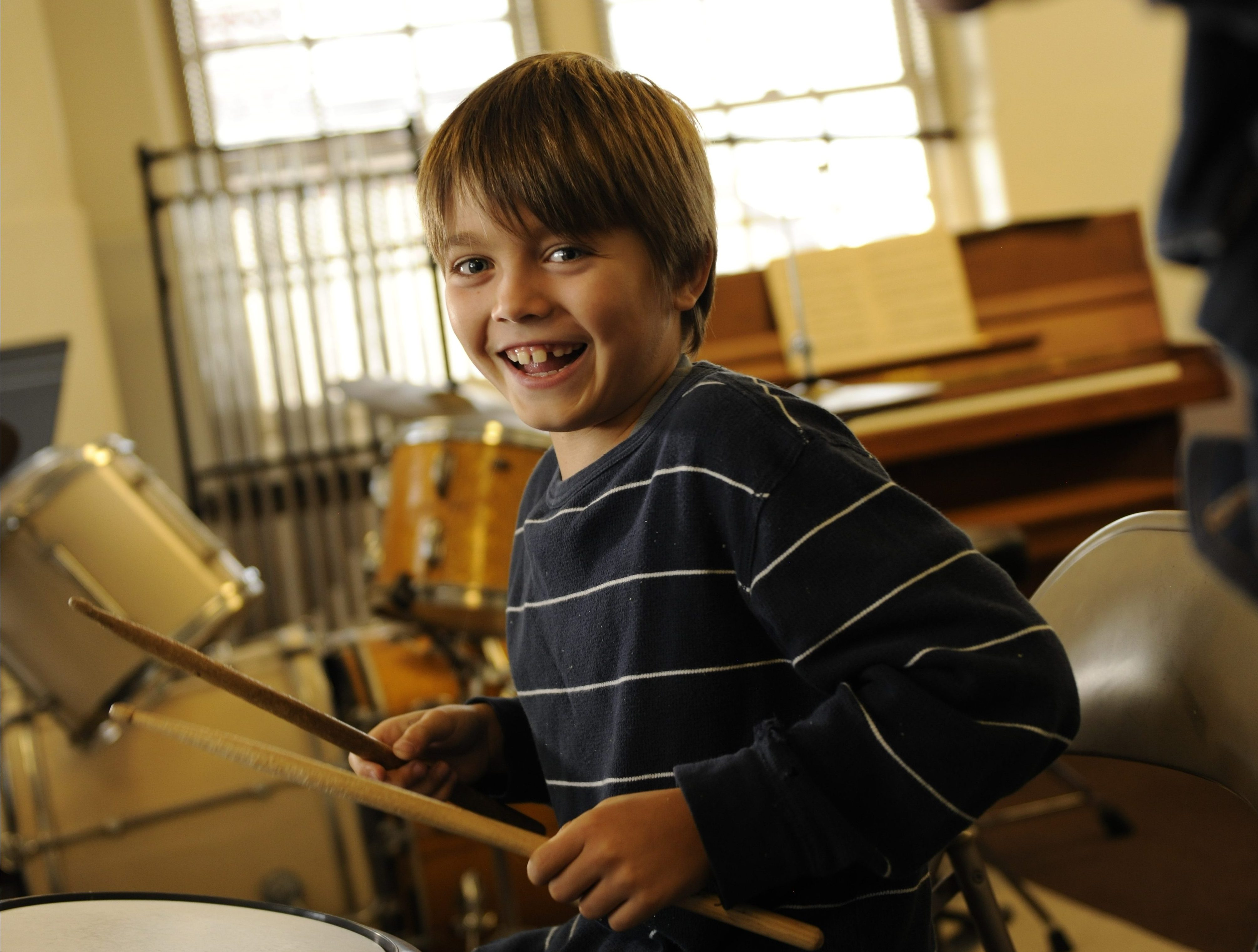 A Settlement student shows off his drumming skills with a smile
