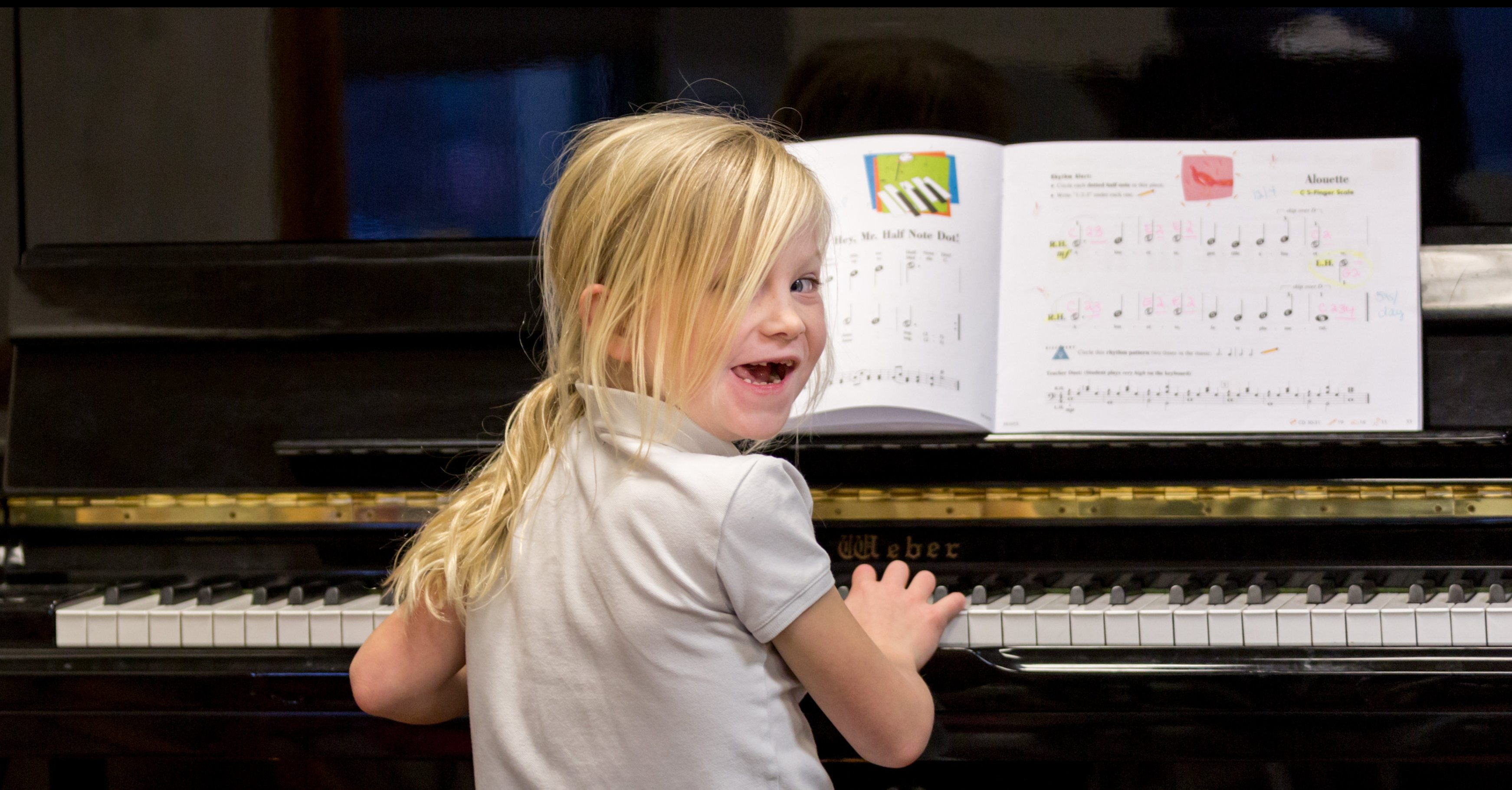 A young student practices piano at Settlement Music School.
