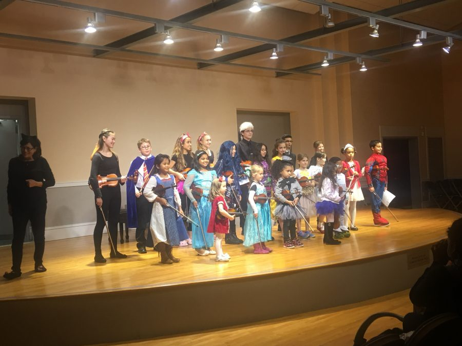 Settlement students perform at a Halloween-themed event.