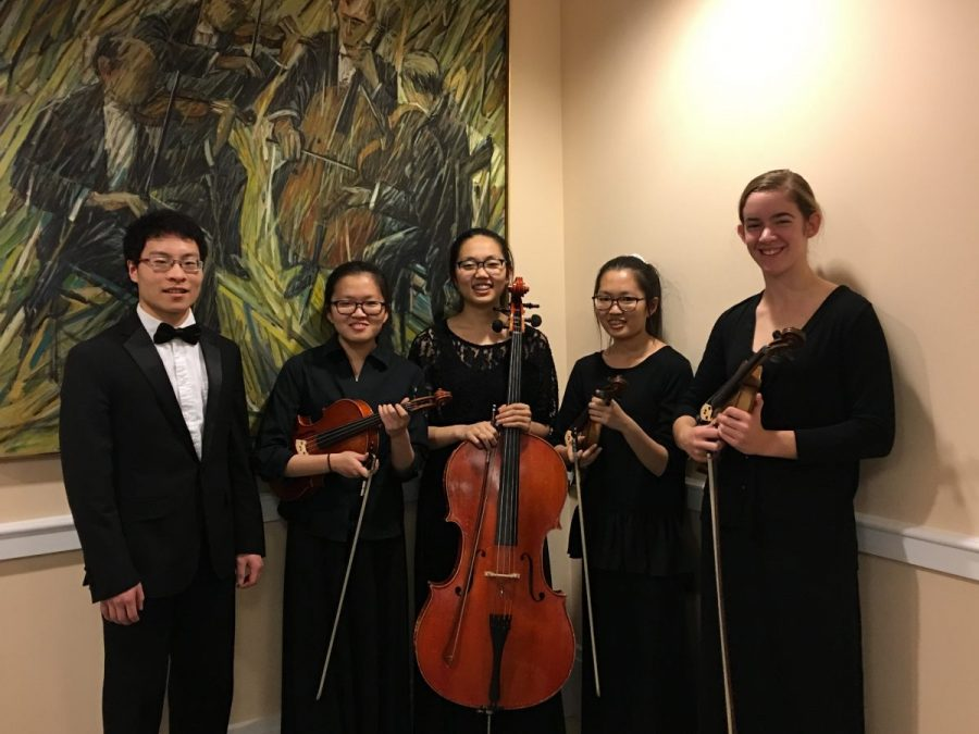 A student ensemble poses for a photo after a performance.