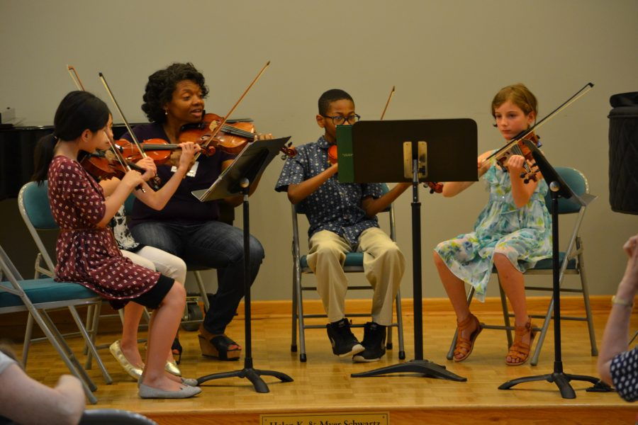 Students of Settlement's Suzuki program rehearse on stage.