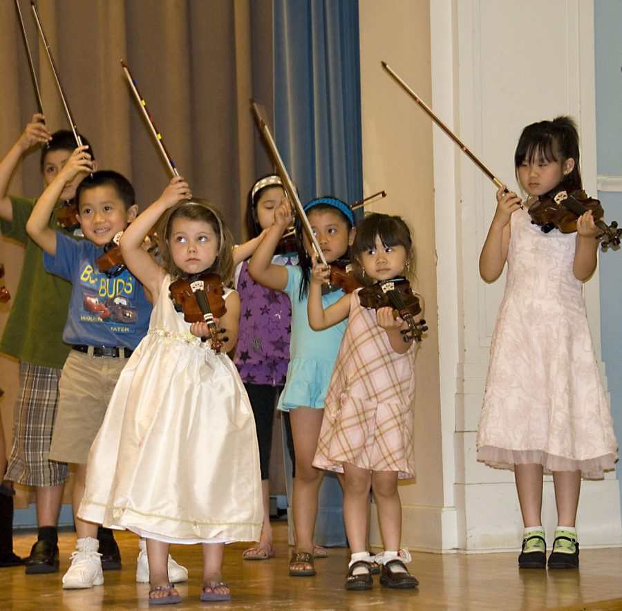 Suzuki students perform on stage at Settlement Music School