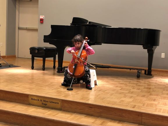 A young student performs on stage at Settlement Music School.