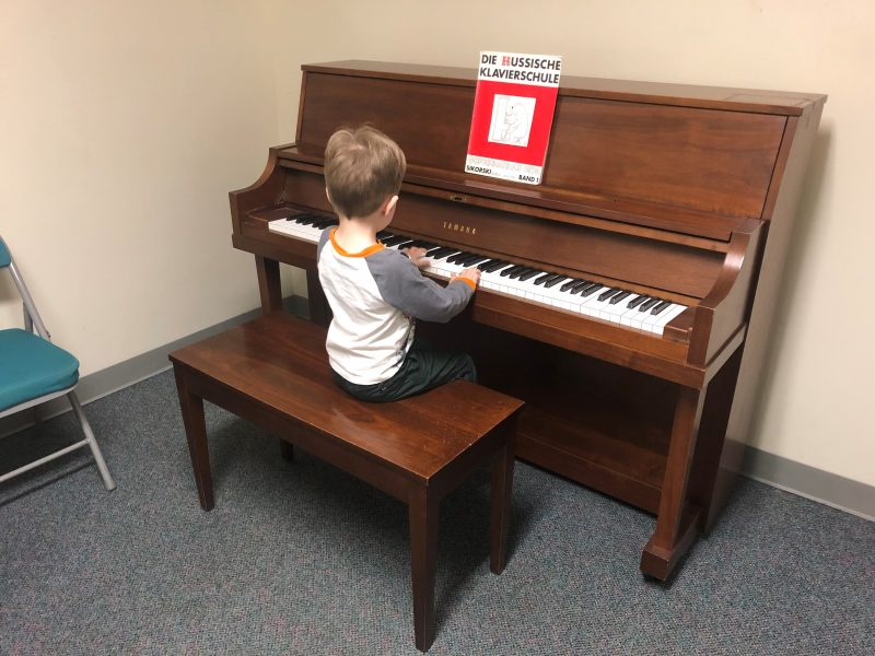 A young Settlement Music School student practices piano